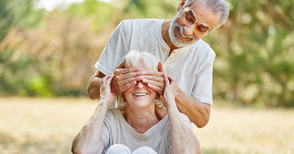older man covers eyes of older woman in field while quizzing her on eye health