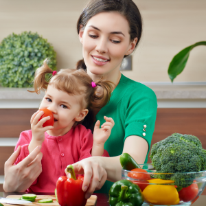 little girl sits in mom's lap and snacks on eye healthy vegetables