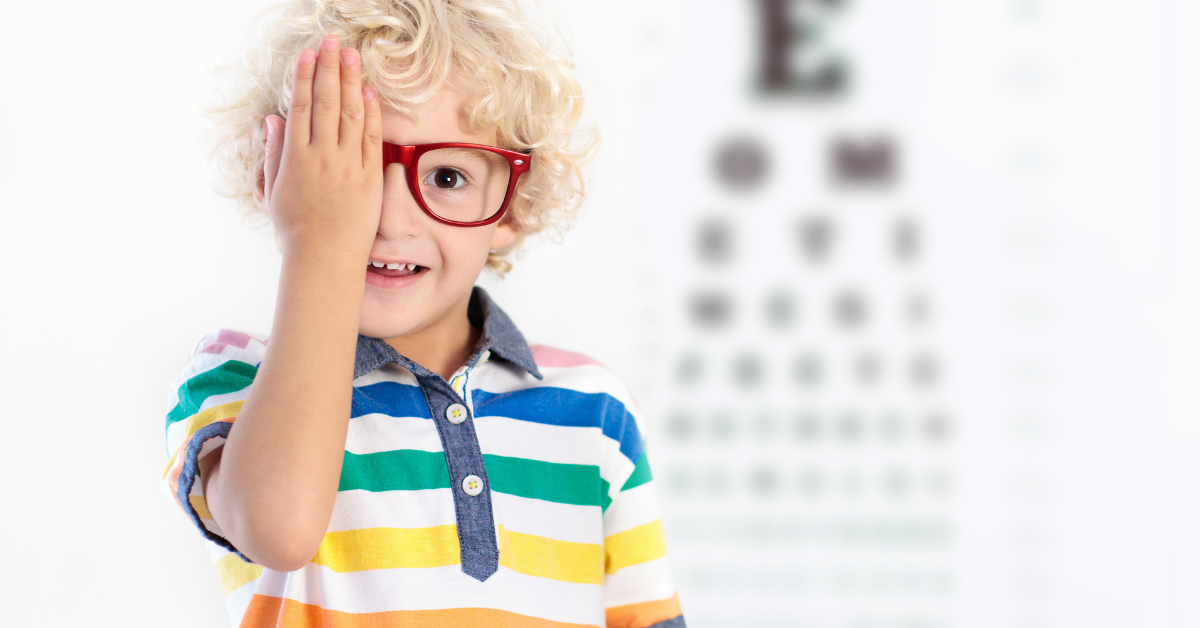 kid covers eye in front of eye chart for eye doctor exam