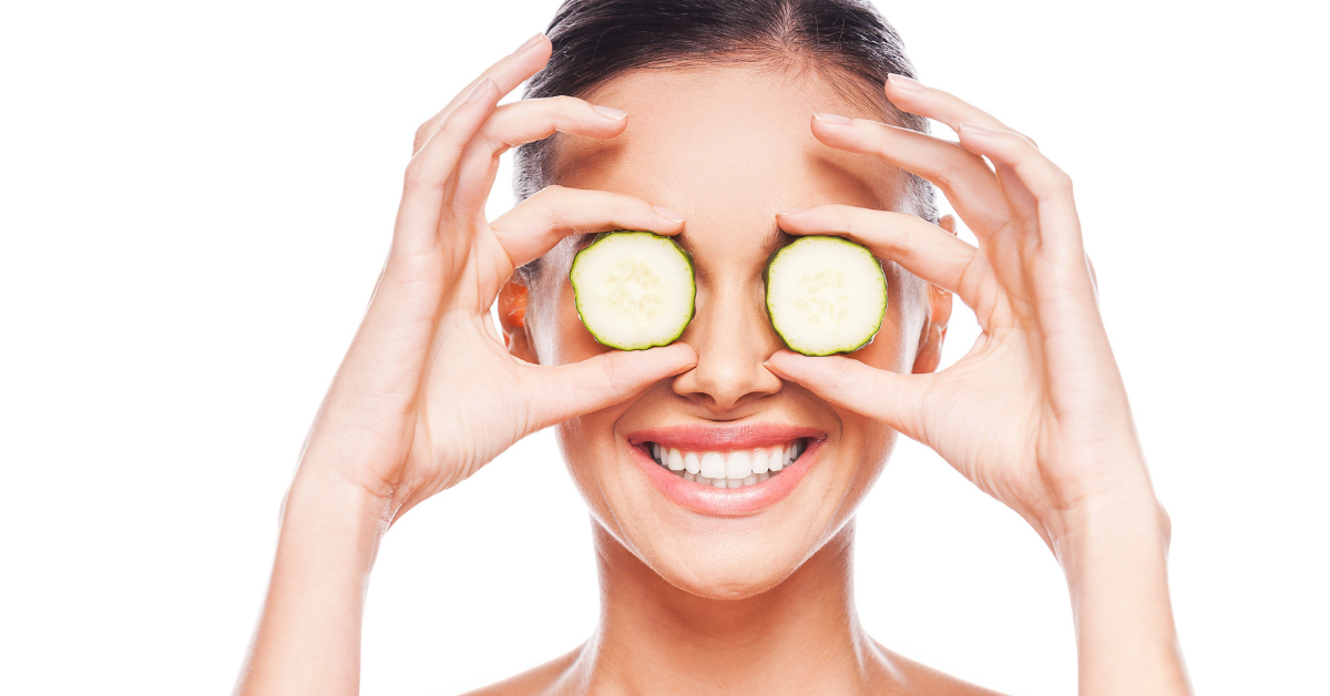 woman holds cucumber in front of eyes while smiling to demonstrate healthy eye habits